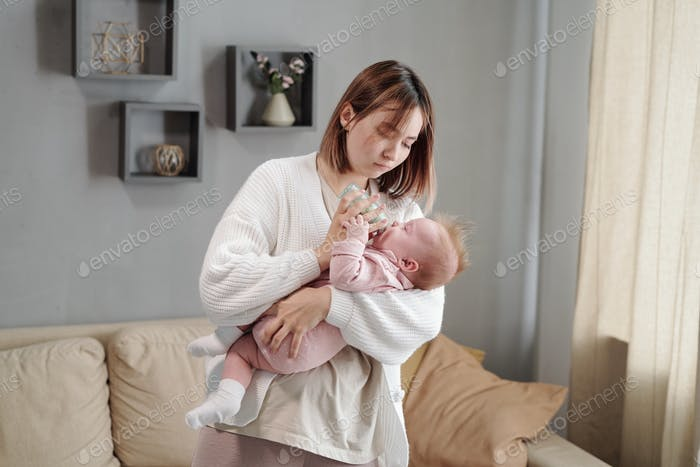 Young woman holding small bottle while feeding her baby daughter