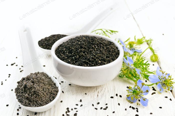 Seeds of black cumin in bowl on board