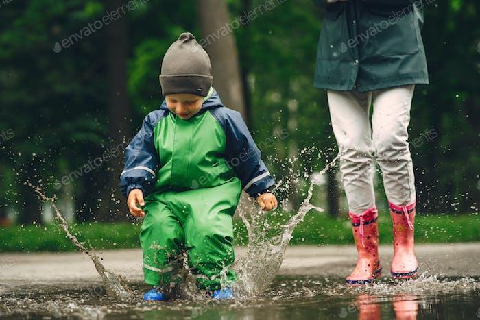 Забавный ребенок в дождевых сапогах, играющий в парке