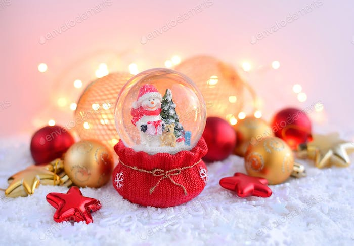 A snow globe with snowman with Christmas decorations and Christm