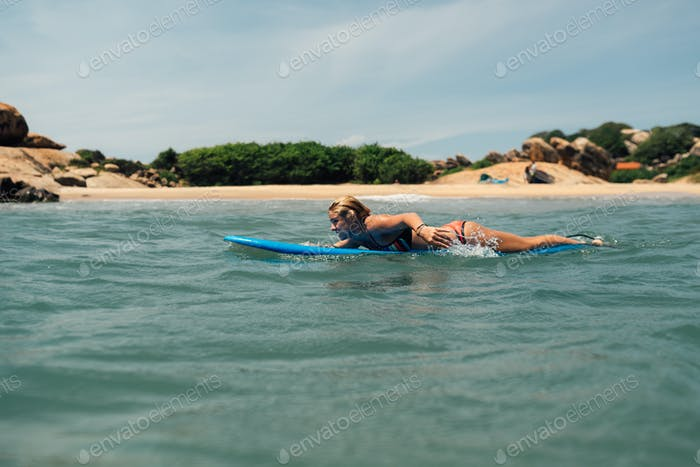 girl floats on a surf catches a wave. Against the shore