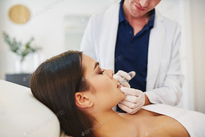 Doctor injecting botox into a young female client's lip