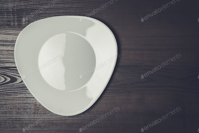 white plate on the wooden brown table background