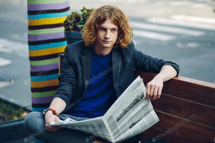 Curly hair man sitting on bench with newspaper