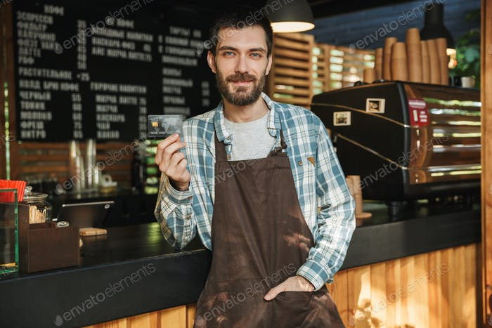 Portrait of caucasian barista man holding credit card while work