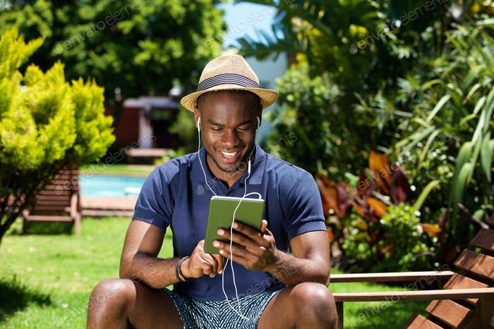 Smiling young african man sitting outdoors using digital tablet