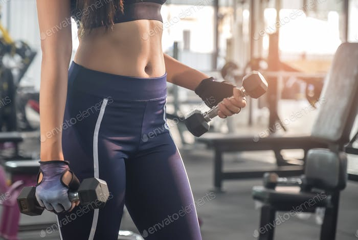 Fitness woman lifting dumbbell in hand.Focus on belly and dumbbell.
