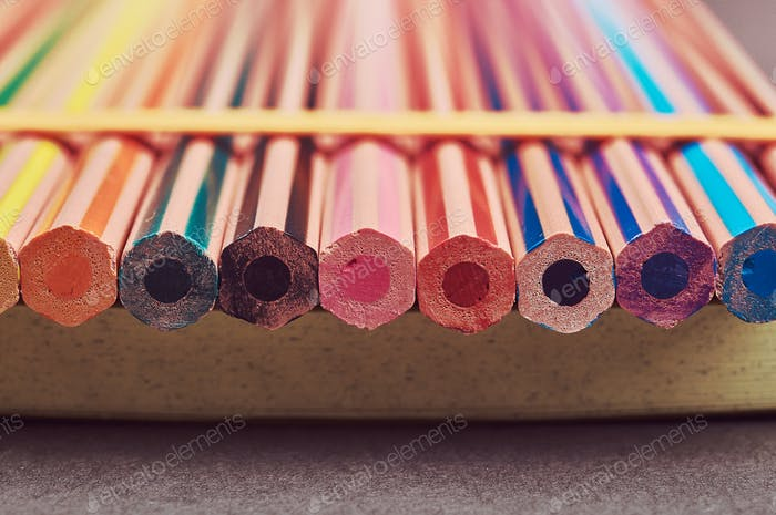 Разноцветные карандаши лежат на желтом блокноте.