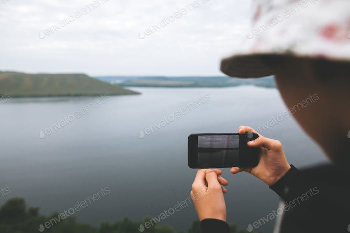 Teenager streaming live while standing on top of rock mountain with amazing view on river