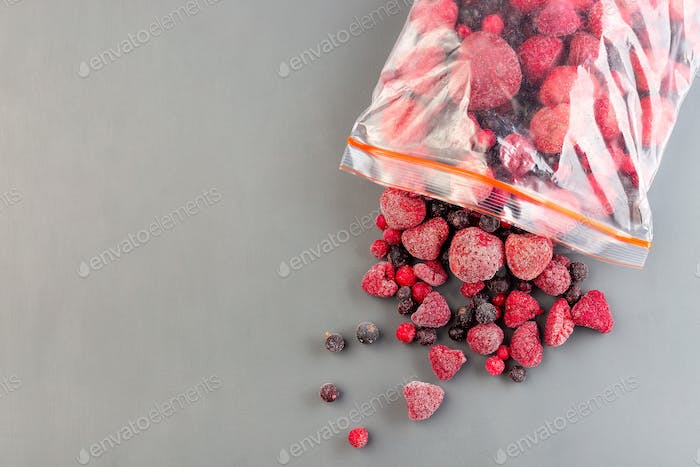 Frozen berries in the plastic bag and on table, horizontal, copy space, top view