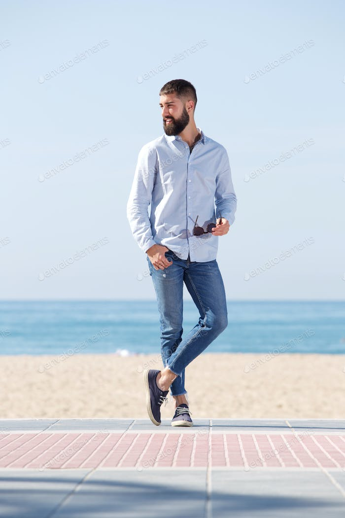 Full length handsome man holding sunglasses and standing on beach