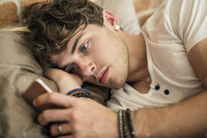 Kaukasier Mann mit Handy im Bett