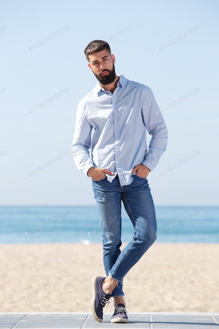 volle Länge ernst gut aussehende Mann stehend durch Strand posiert