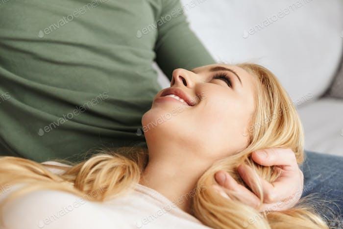 Niedlich lächelnde junge Frau liegt auf ihrem Mann