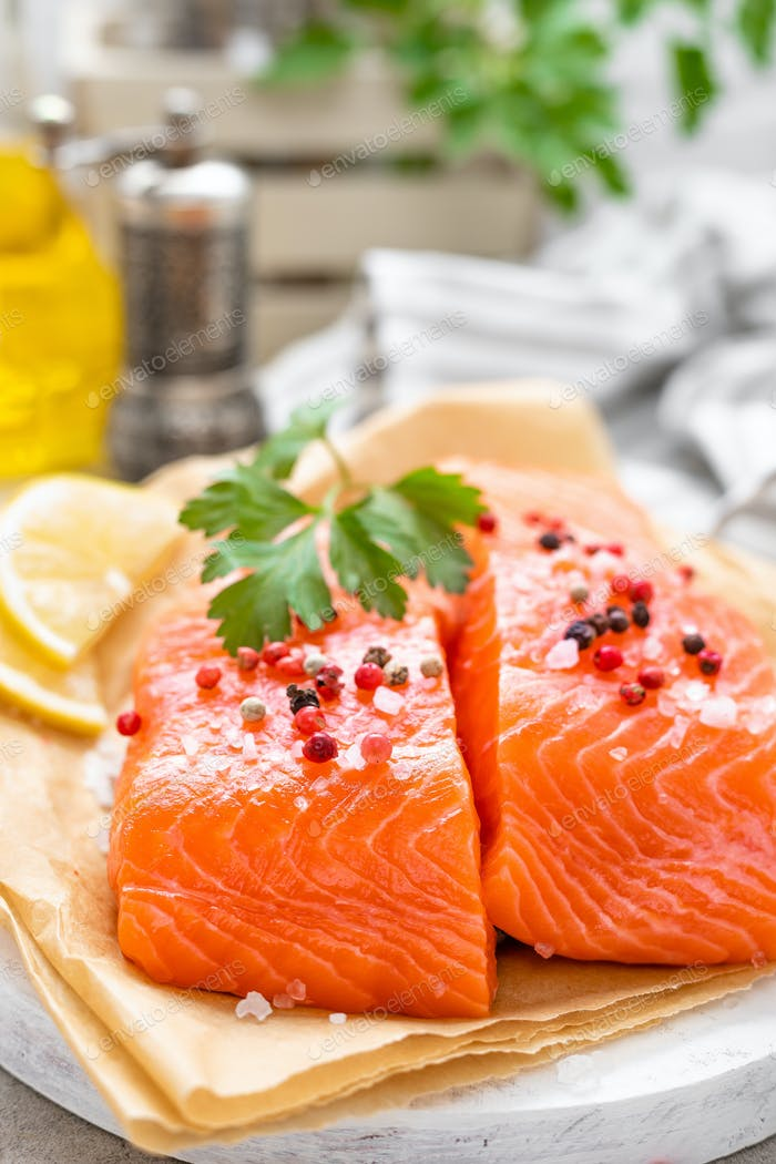 Fresh raw salmon fish fillet on white kitchen background