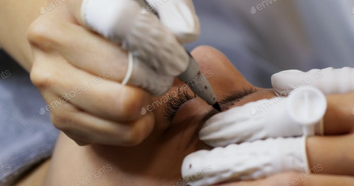 Woman having microblading eyebrows in a beauty salon