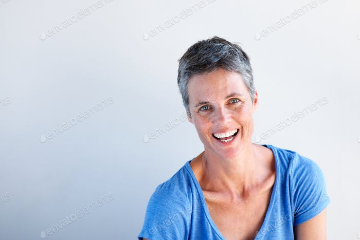 Close up happy mature woman laughing against white background