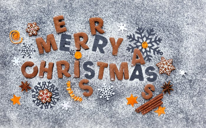 Merry Christmas cookies on a snowy flour with a dark background,