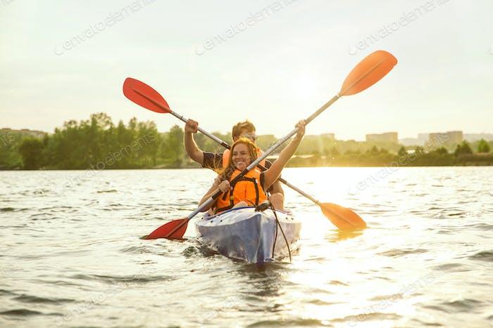 Glückliches Paar Kajakfahren auf Fluss mit Sonnenuntergang auf dem Hintergrund