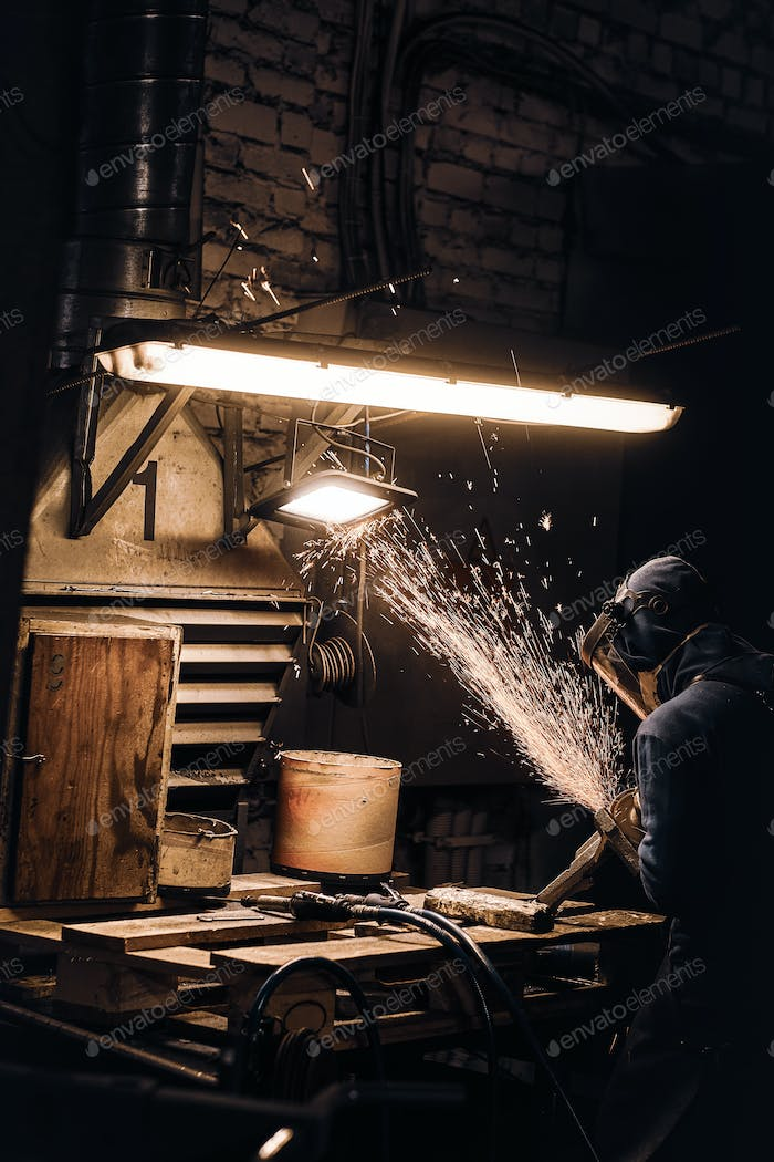 Diligent man is working with metal at workshop