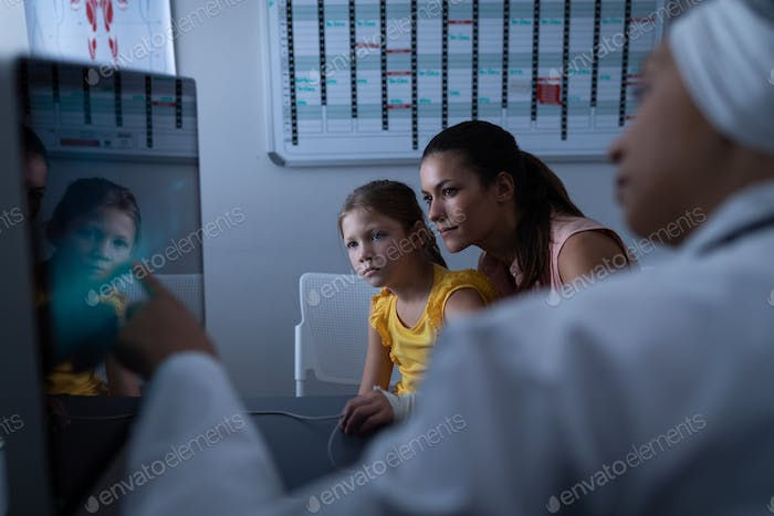 Mature female doctor showing medical report to patient with computer in clinic at hospital