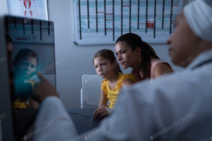 Reife Ärztin zeigt medizinischen Bericht an Patienten mit Computer in Klinik im Krankenhaus