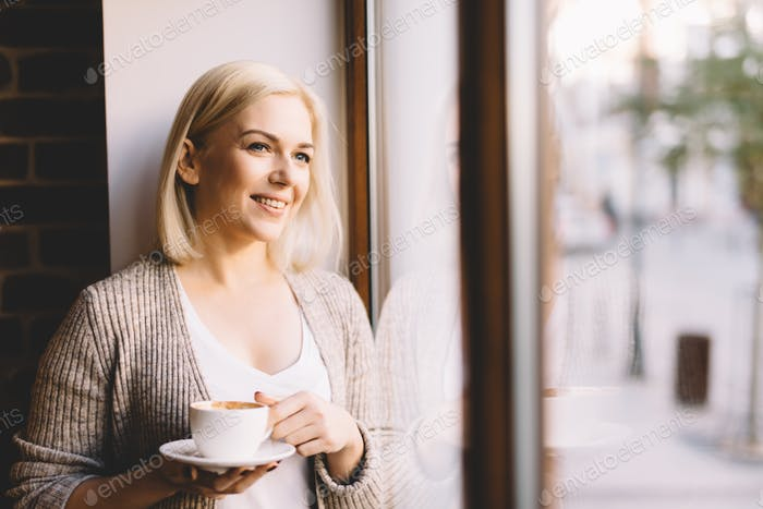 Woman with a cup of coffee standing by the window.