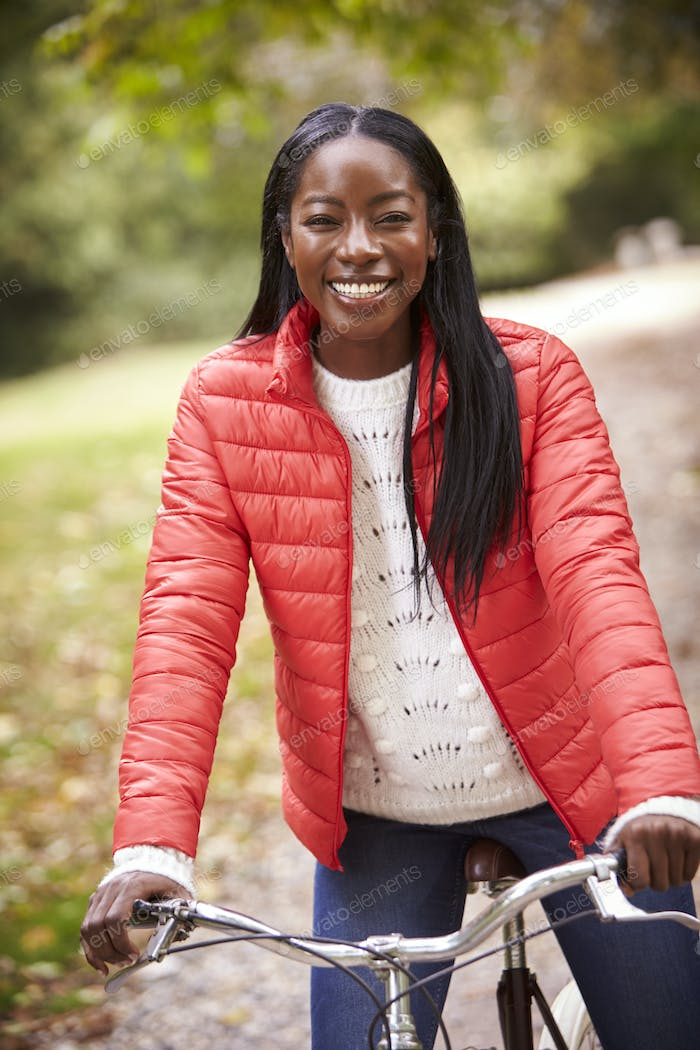 Young adult black woman sitting on a vintage bicycle in a park smiling to camera