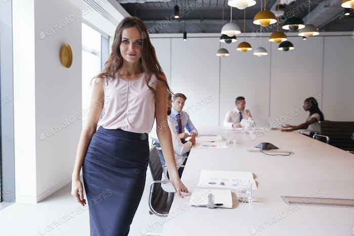 Портрет бизнесвумен стоя в современном зале заседаний