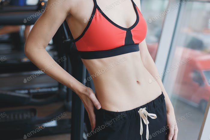 Slim young woman body at gym
