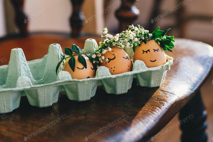 Stylish easter eggs in floral wreath and sleeping cute faces in carton tray