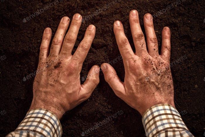Agricultores manos en suelo fértil
