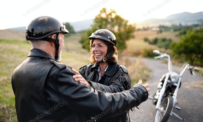 Cheerful senior couple travellers with motorbike in countryside, talking.