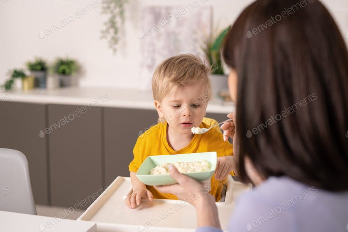 Cute little boy eating homemade porridge while mother holding spoon by his mouth