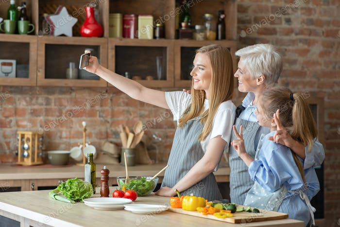 Daughter, mother and grandmother taking selfie while making dinner together
