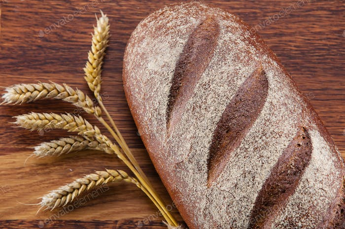 Loaf of bread and wheat over wooden background