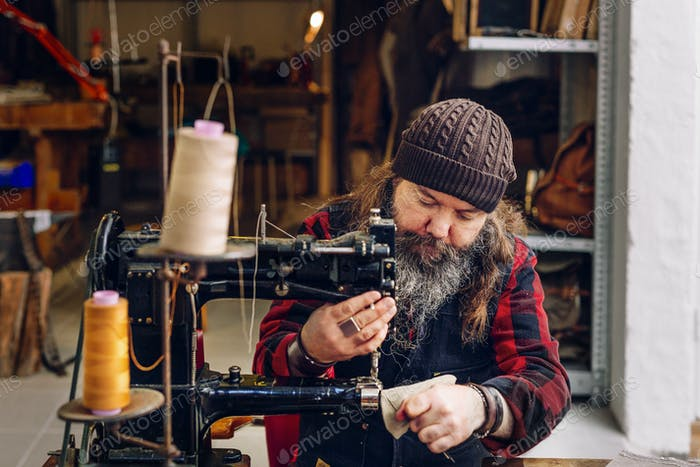 Male worker sewing bag pocket in workshop