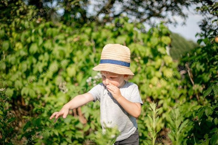 Kleines Kind, das im Garten des Gartens spielt