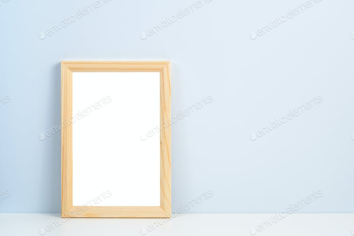 Wooden photo frame standing on shelf