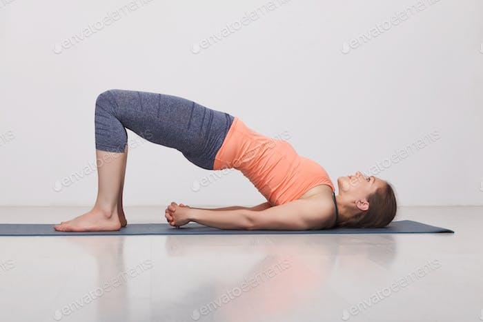 Beautiful sporty fit yogi girl practices yoga asana setu bandhas