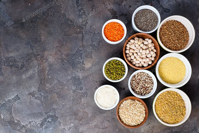 Superfoods and cereals selection in bowls on grey concrete background