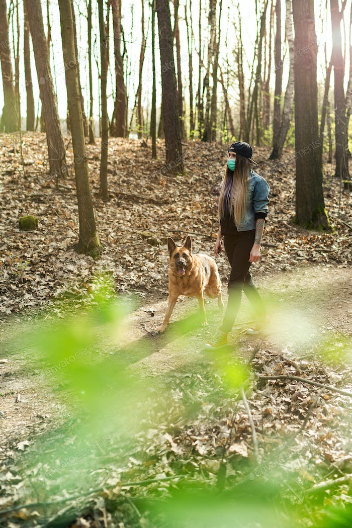 Casual Woman Walking Dog in Forest while Wearing Protective Face Mask.