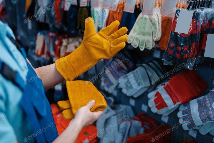 Рабочий в униформе надевает перчатки в инструментальном магазине