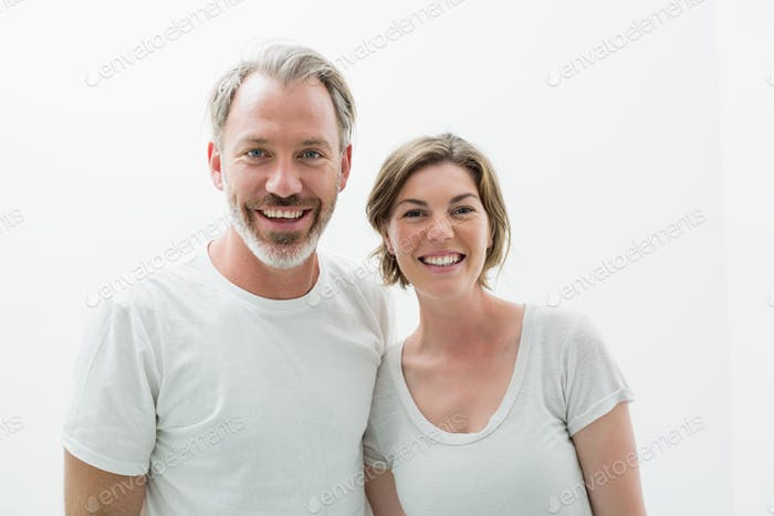 Smiling couple in white t-shirt in bedroom at home