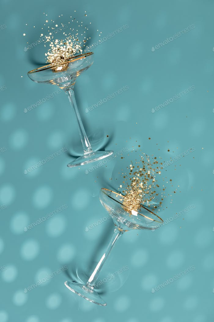 Two champagne glasses with splash of confetti over creative background
