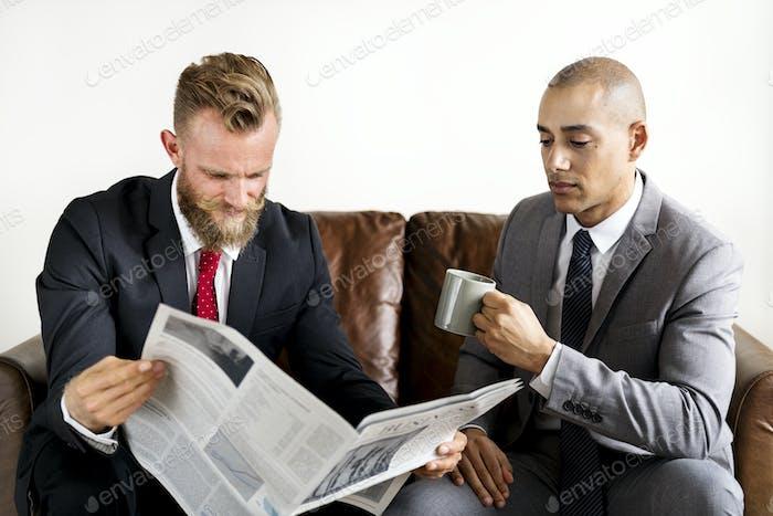 Zwei Geschäftsmann sitzt auf einer Couch