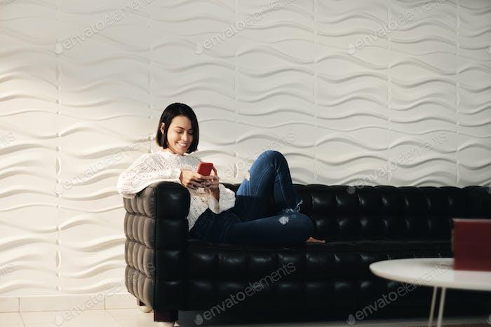 junge hispanische mädchen messaging mit handy auf sofa
