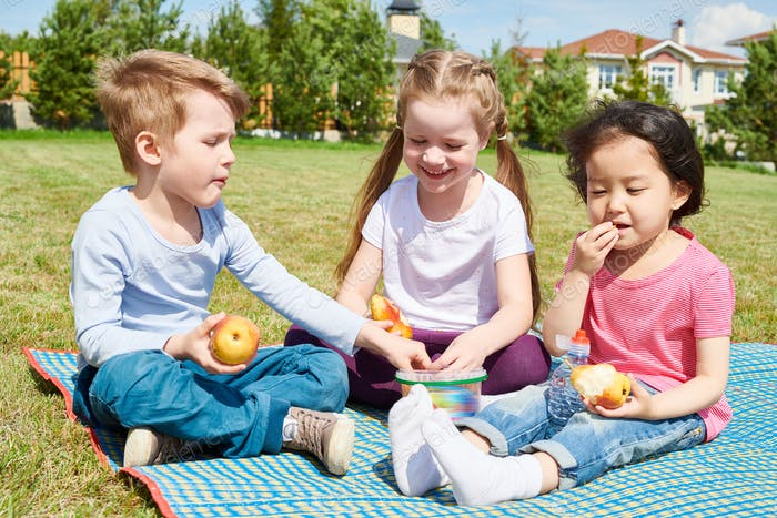 Kids Enjoying Picnic on Lawn