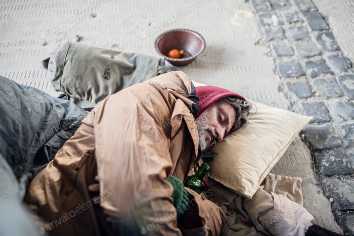 Homeless beggar man lying on the ground outdoors in city, sleeping.