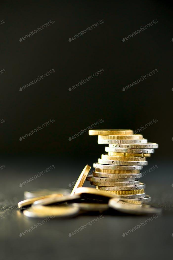 Euro-Geld, Währung. Erfolg, Reichtum und Armut, Armen Konzept. Euro-Münzen stapeln auf dunklem Schwarz